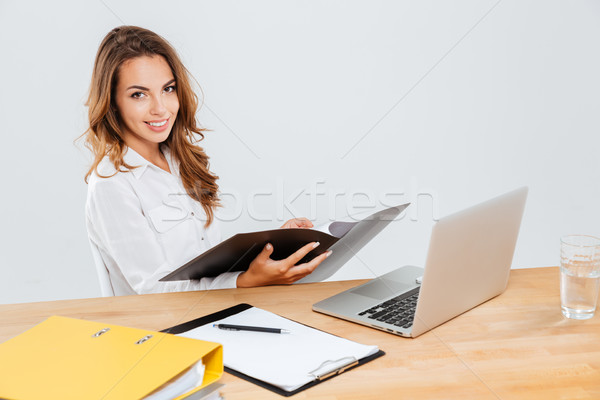 Smiling young businesswoman woking with documents and laptop Stock photo © deandrobot