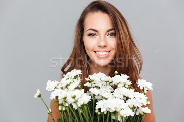 Glimlachend jonge vrouw bos witte bloemen portret grijs Stockfoto © deandrobot