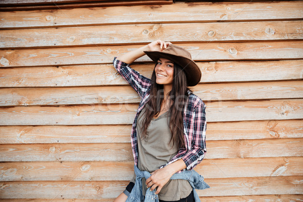 Happy attractive young woman cowgirl standing and smiling Stock photo © deandrobot