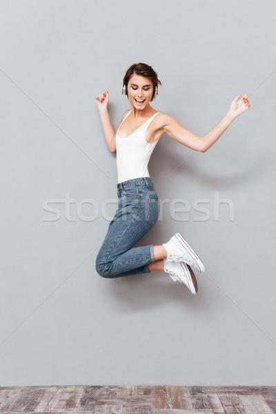 Nő hallgat zene fejhallgató ugrik levegő Stock fotó © deandrobot