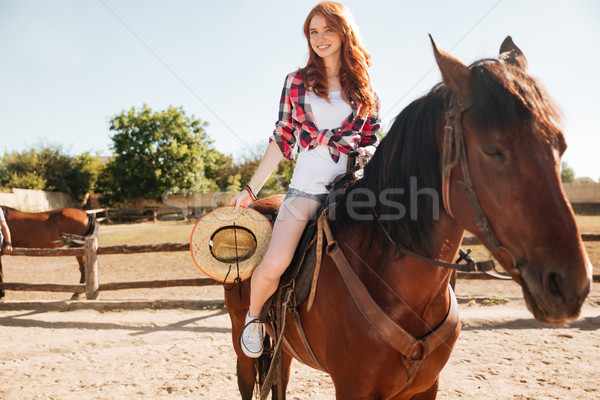 Smiling woman cowgirl riding horse in village Stock photo © deandrobot