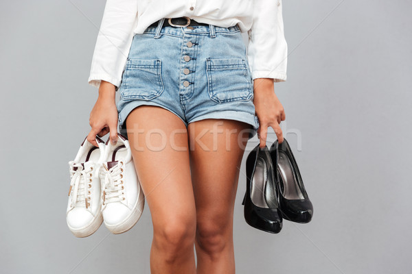 Young girl in denim shorts holding two pairs of shoes Stock photo © deandrobot
