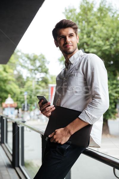 Empresário em pé celular ao ar livre bonito jovem Foto stock © deandrobot