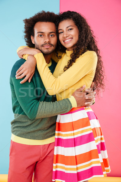 Smiling african young couple standing and hugging Stock photo © deandrobot