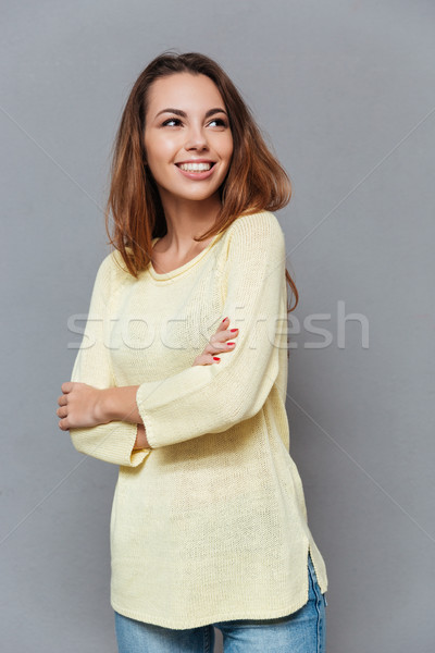 Woman in sweater standing with arms folded and looking away Stock photo © deandrobot