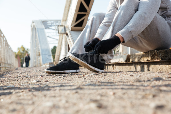 Cropped image of a sports man tying shoe laces Stock photo © deandrobot