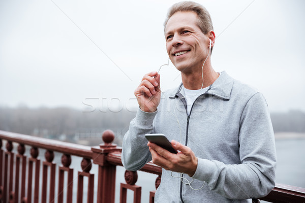 Runner listening to music on bridge Stock photo © deandrobot