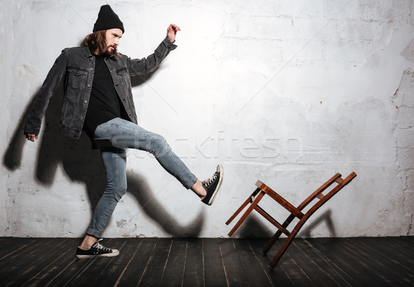 Portrait of a bearded hipster man kicking chair with foot Stock photo © deandrobot