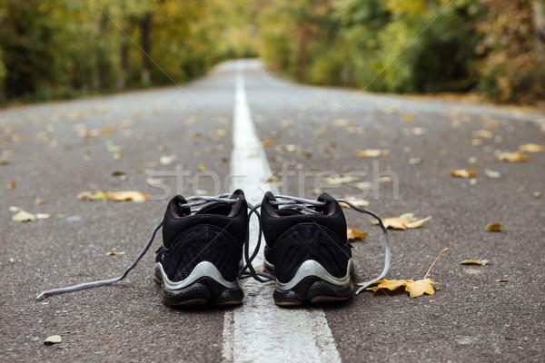 Close up new black running shoes on asphalt road Stock photo © deandrobot