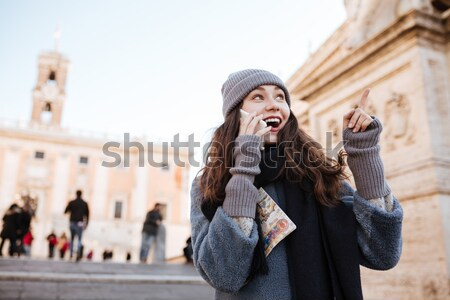 Surprised woman talking on mobile phone pointing away in city Stock photo © deandrobot