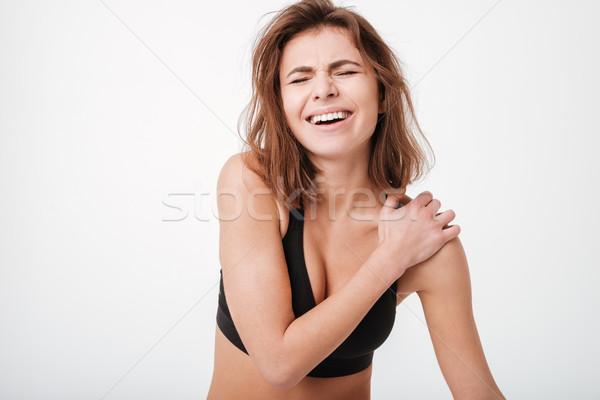 Sad frowning young woman athlete having shoulder pain Stock photo © deandrobot