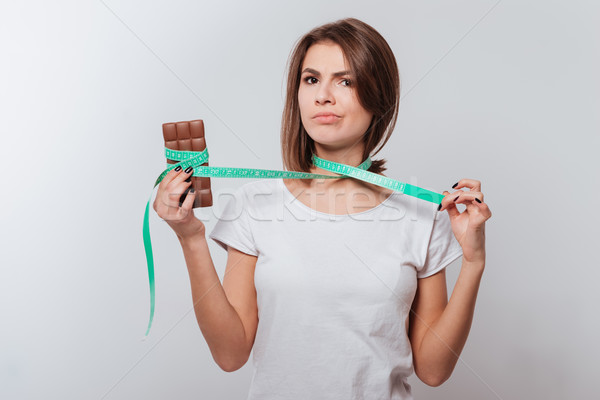 Young lady holding centimeter and chocolate Stock photo © deandrobot