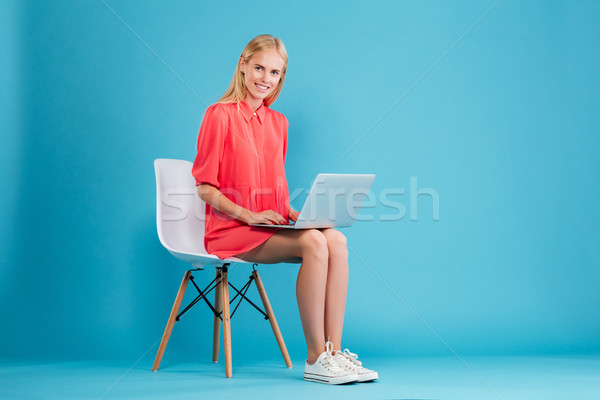 Smiling pretty woman in red dress with laptop computer Stock photo © deandrobot