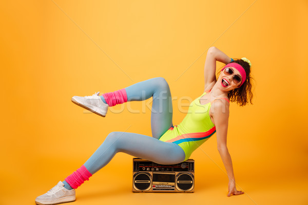 Cheerful charming young fitness woman sitting and posing on boombox Stock photo © deandrobot