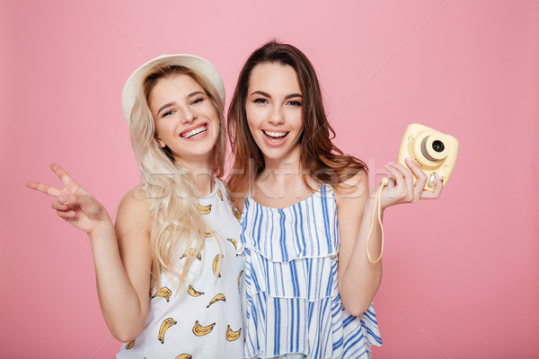 Two cheerful lovely young women standing and holding photo camera Stock photo © deandrobot