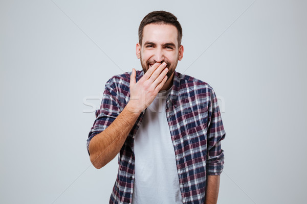 Laughing Bearded man in shirt covering mouth Stock photo © deandrobot