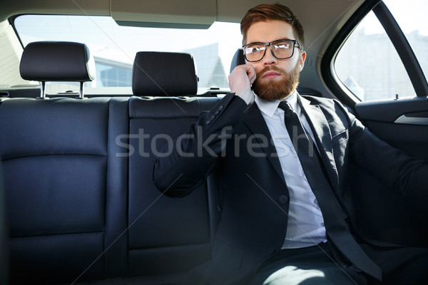 Young serious businessman sitting in car and talking on phone Stock photo © deandrobot