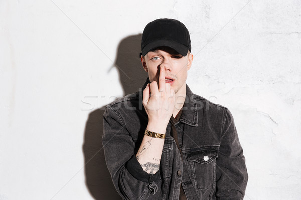 Hipster in snap back showing middle finger Stock photo © deandrobot