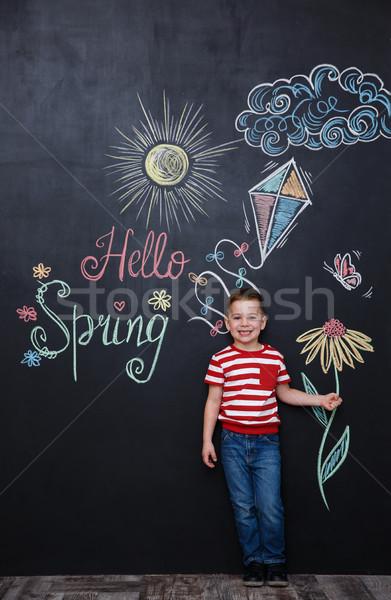 Little cute boy holding flower on the chalk black board Stock photo © deandrobot