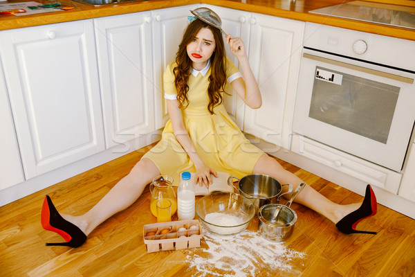 Sad pin-up woman sitting on floor at kitchen Stock photo © deandrobot