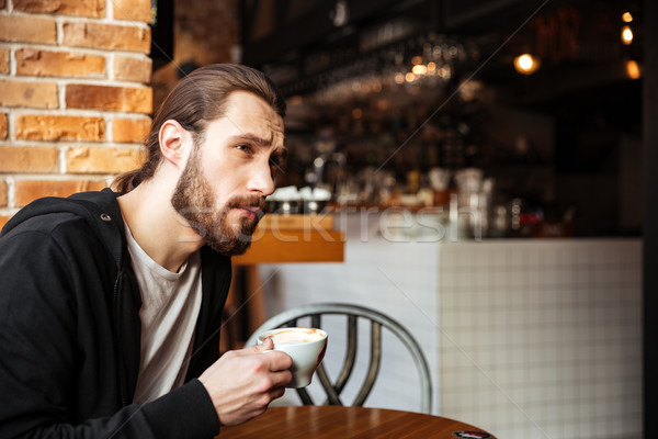 Side view of Serious Bearded man in cafe Stock photo © deandrobot