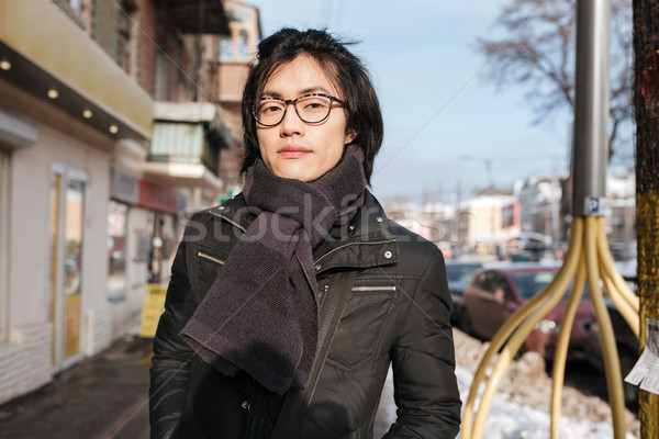 Amazing young asian man wearing glasses and scarf walking Stock photo © deandrobot