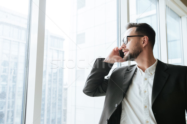 Bearded business man talking on phone and looking away Stock photo © deandrobot