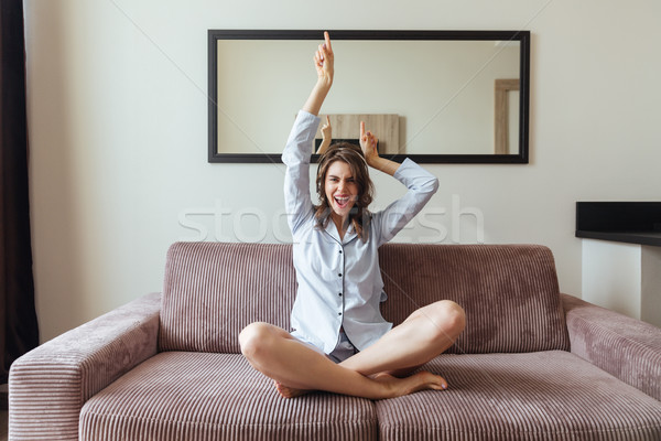 Emotional young lady dressed in pajama listening music. Stock photo © deandrobot