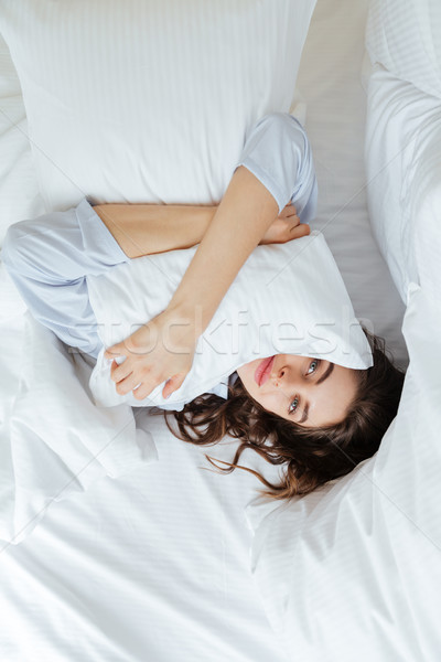 Cheerful young lady dressed in pajama lies in bed Stock photo © deandrobot