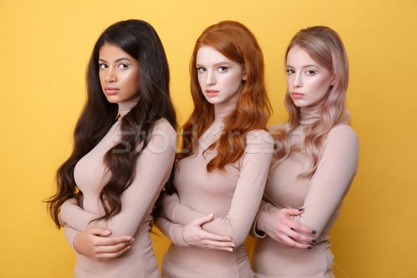 Three ladies with crossed arms posing in studio Stock photo © deandrobot
