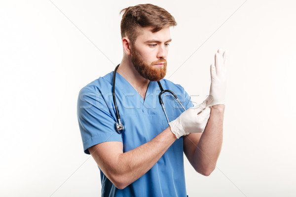 Portrait of a concentrated young doctor putting on sterile gloves Stock photo © deandrobot