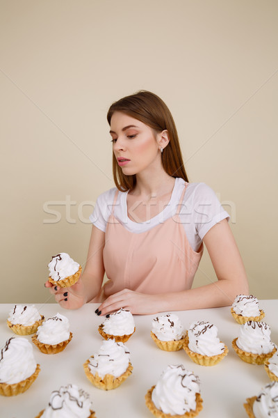 Vertical image of pensive woman by the table eating cakes Stock photo © deandrobot