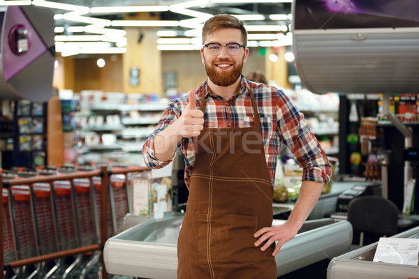 Stock photo: Happy cashier man on workspace shop showing thumbs up.