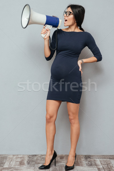 Screaming pregnant business lady holding loudspeaker. Stock photo © deandrobot