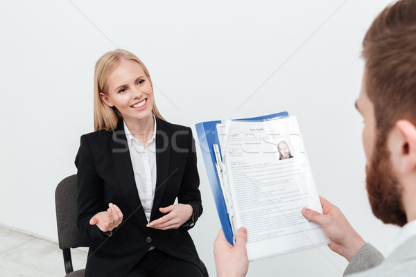 Happy lady sitting in office near her boss holding resume Stock photo © deandrobot