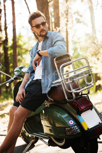 Handsome young bearded man standing near scooter outdoors Stock photo © deandrobot
