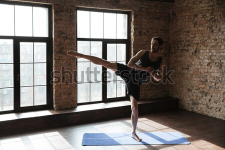 Portrait of a young healthy man in sportswear doing stretching Stock photo © deandrobot