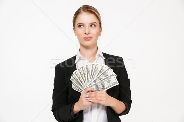 Smiling pensive blonde business woman holding money and looking away Stock photo © deandrobot