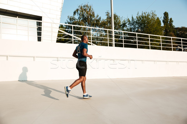 Full length portrait of a young african sportsman in earphones Stock photo © deandrobot