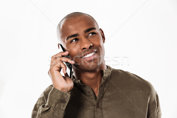 Pleased african man talking by the smartphone and looking away Stock photo © deandrobot