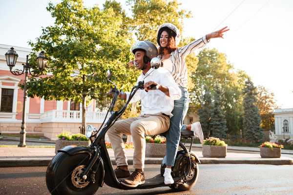 Full length picture of happy african couple rides on motorbike Stock photo © deandrobot