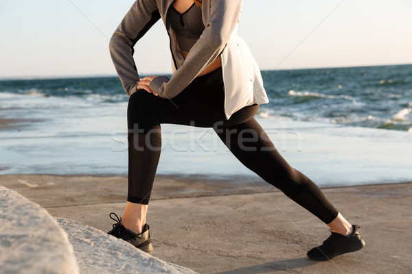 Cropped photo of sport wooman doing stretch exercise at seaside Stock photo © deandrobot