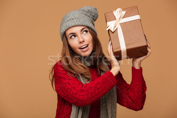 Young charming woman in red knitted sweater holding gift box, lo Stock photo © deandrobot