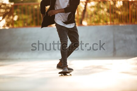 Afro american man performing a trick on a skateboard Stock photo © deandrobot