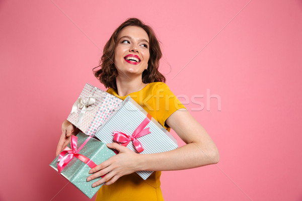 Cheerful young woman in yellow dress holding heap of presents Stock photo © deandrobot