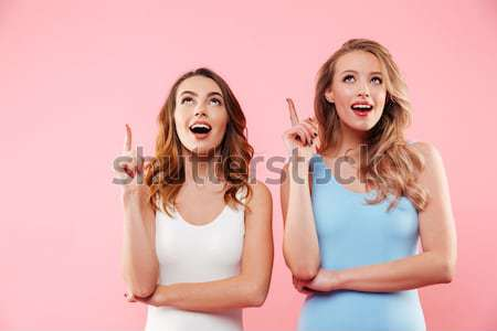Two overjoyed young girls in colorful tshirts showing winner ges Stock photo © deandrobot