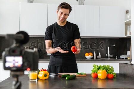 Joyful young man filming his video blog episode Stock photo © deandrobot