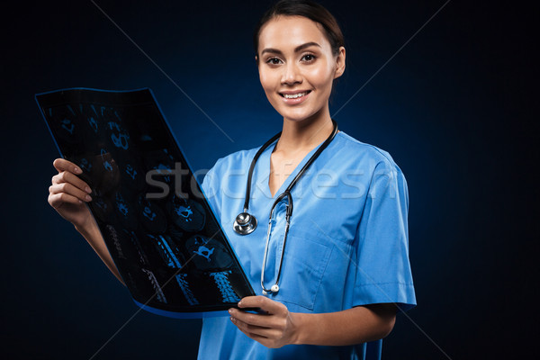 Brunette smiling doctor in uniform looking at x-ray image Stock photo © deandrobot