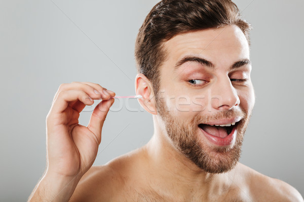 Close up portrait of a cheery man cleaning his ears Stock photo © deandrobot