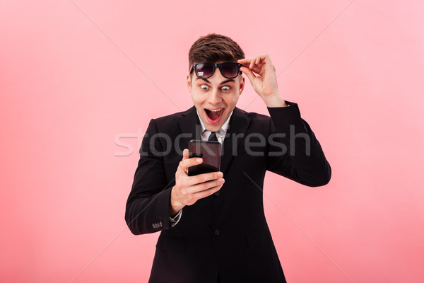 Surprised happy man using smartphone isolated Stock photo © deandrobot